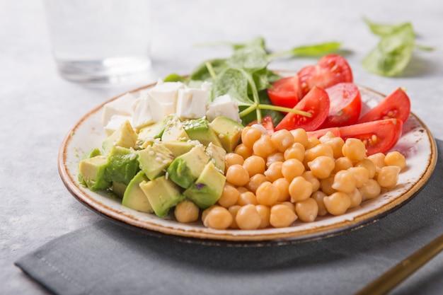 Ciotola del buddha con avocado, ceci, formaggio feta, spinaci freschi, pomodori e bicchiere d'acqua.