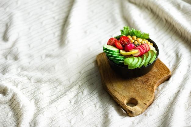 Ciotola di buddha con avocado, quinoa, cetriolo, ravanello, insalata, limone, pomodorini, ceci, semi di chia