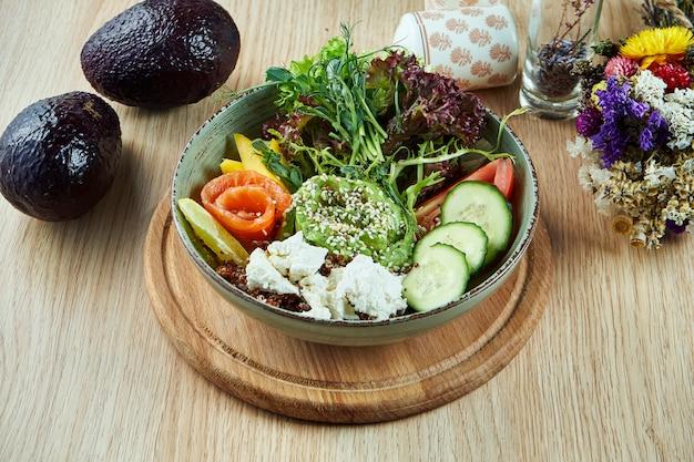 Ciotola di buddha con cetrioli, pomodori, guacamole e salmone, formaggio feta e lattuga su un tavolo di legno. cibo sano ed equilibrato. nutrizione fitness. vista dall'alto, cibo piatto laico.