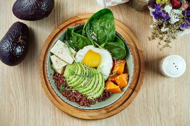 Ciotola di buddha con quinoa, zucca, spinaci, tofu e uovo fritto. cibo sano ed equilibrato. nutrizione fitness. vista dall'alto, cibo piatto laico.