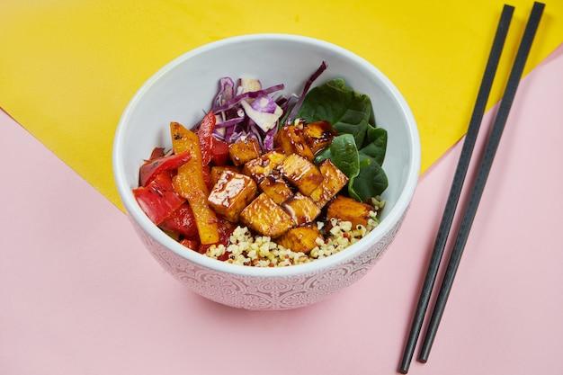 Ciotola di buddha con tofu in salsa agrodolce, peperoni, cavoli e spinaci su superfici colorate. cibo vegetariano sano