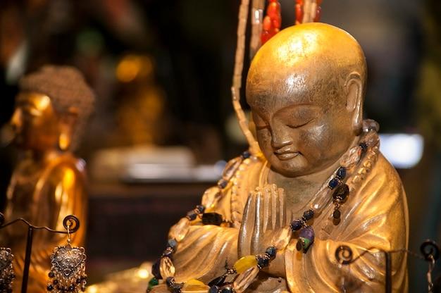 Figura di buddha in preghiera e meditazione adornata e circondata da altri spiritual