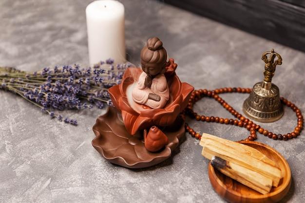 La figura del buddha con un aroma di fumo dai bastoncini di incenso bruciati svolazza