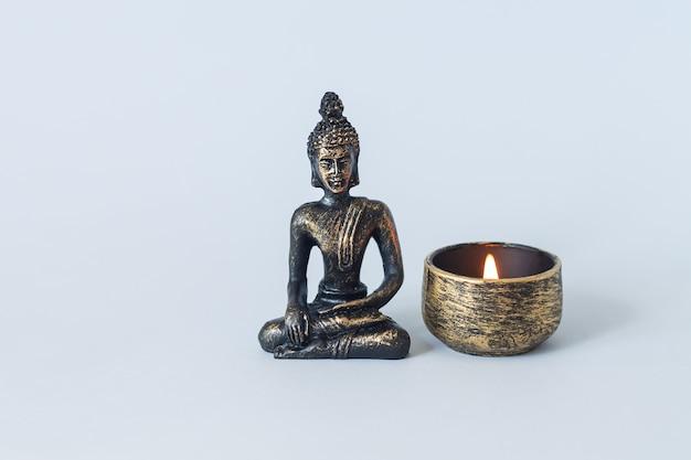 Statua del buddha sull'altare con candela accesa. meditazione, buddismo e concetto di illuminazione