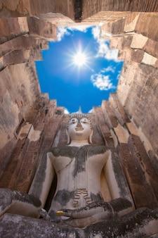 Statua di buddha nel cielo con il sole durante il giorno.