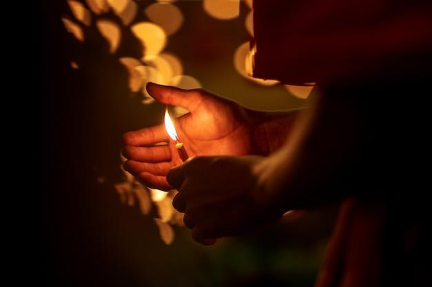 Mani del monaco buddista che tengono candela di illuminazione