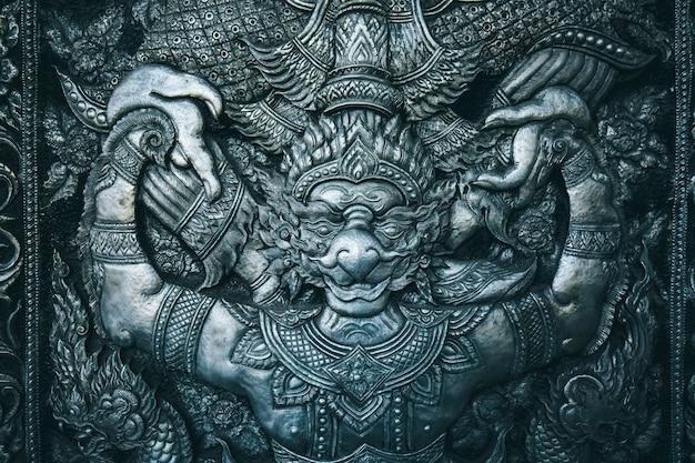 Statua di scultura in acciaio buddista garuda su sfondo nero il tempio della porta in thailandia