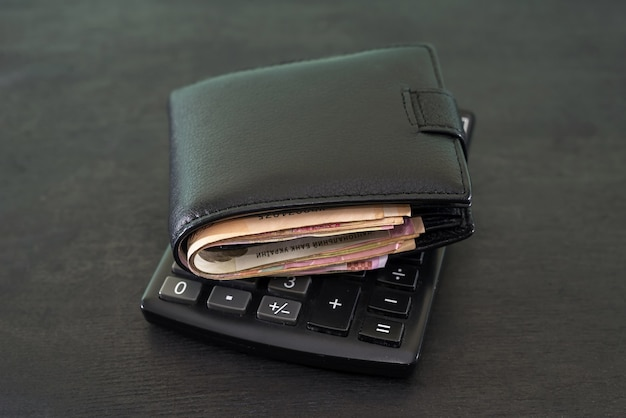 Concetto di budget e denaro. portafoglio pieno di soldi con una calcolatrice su una tavola nera.