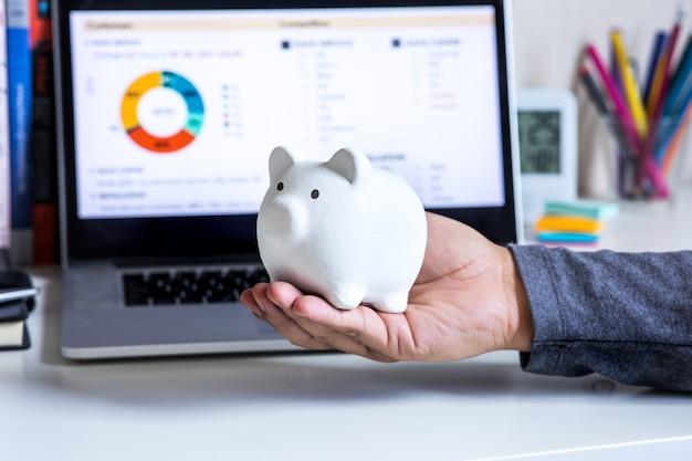 Concetti di budget e risparmio con piggy a portata di mano sulla scrivania ufficiofinanziario e gestionale