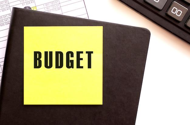 Budget testo su un adesivo sul desktop. diario e calcolatrice. concetto finanziario.