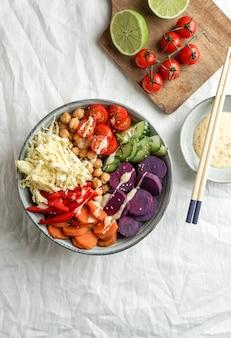 Ciotola di budha con batata viola, peperoni, cavolo cappuccio, patate dolci, ceci, cetrioli sulla tovaglia di lino bianca