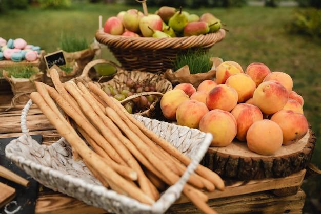 Un tavolo da buffet pieno di vari frutti come una mela e una pera con le bacchette italiane