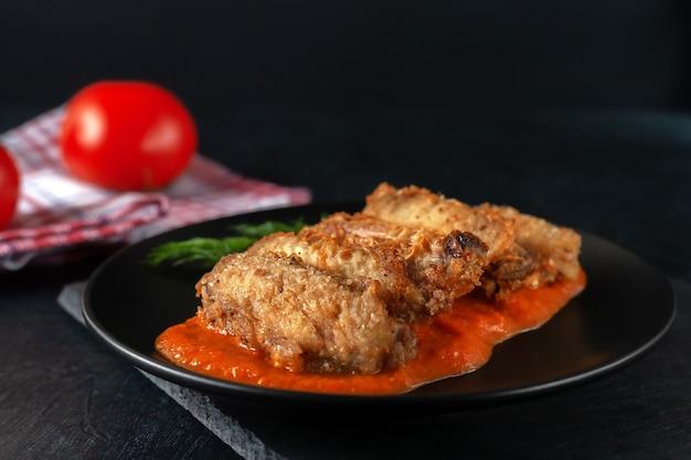 Primo piano delle ali di buffolo in ciotola di ceramica con salsa di pomodoro e pomodori