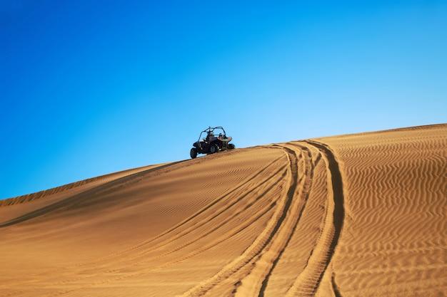 Buggy quad drive sulla collina di sabbia del deserto e lascia le tracce delle ruote