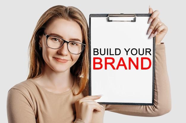 Costruisci il tuo marchio. la bella giovane donna di affari che indossa gli occhiali tiene una lavagna per appunti con mock up spazio isolato su sfondo grigio