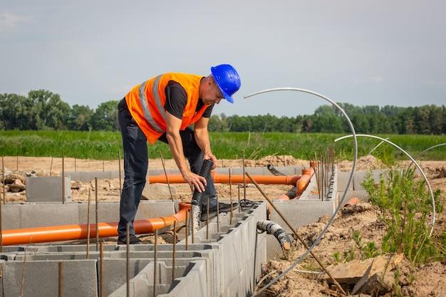 Builder che controlla la fondazione del bungalow della casa, concetto di costruzione