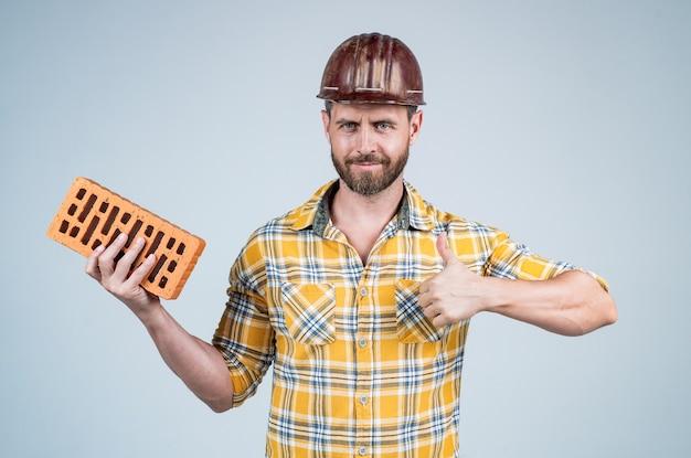 Il costruttore gode del successo. architetto uomo con mattoni. ragazzo indossa l'uniforme da lavoratore. bel costruttore in casco. l'uomo maturo indossa una camicia a scacchi. costruttore o meccanico professionista. ingegnere edile.