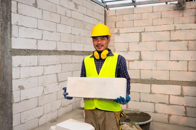 Il costruttore tiene mattoni aerati sterilizzati in autoclave. il concetto propone di utilizzare mattoni aerati sterilizzati in autoclave nella costruzione di case.