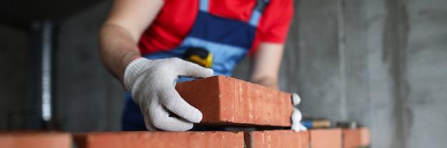 Il costruttore fa un muro di mattoni in un primo piano della casa