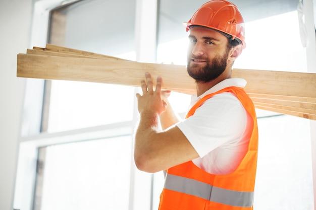 Uomo del costruttore in elmetto protettivo che trasporta legname in cantiere da vicino