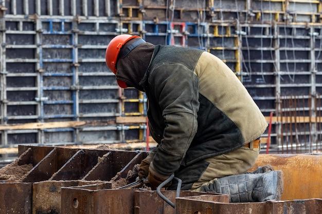 Un costruttore con un casco arancione è impegnato nella saldatura in un cantiere, rafforzando le strutture metalliche della base dell'edificio