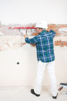 Un costruttore con un casco protettivo controlla un muro di mattoni piatto con un livello di edificio durante la riparazione di una casa