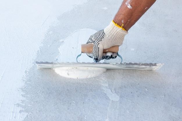 Builder utilizzando strumento di intonacatura per la finitura di pareti e pavimenti.