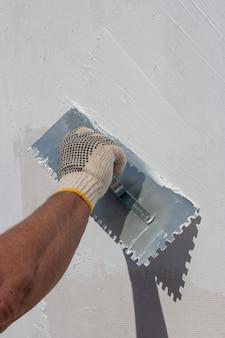 Builder utilizzando strumento di intonacatura per la finitura della parete.