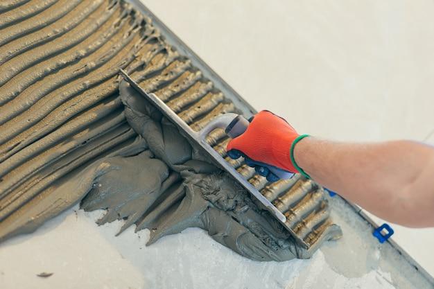 Un costruttore che installa il pavimento con grandi piastrelle di ceramica durante i lavori di riparazione