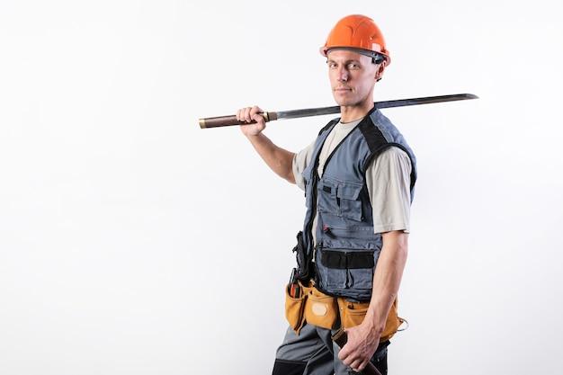 Un costruttore con una grossa spada sulla spalla. riparatore che indossa un casco e abiti da lavoro. per qualsiasi scopo.