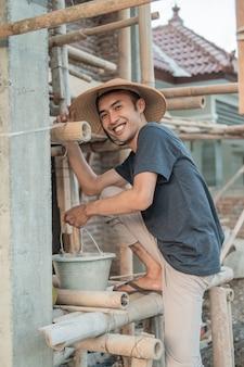 Costruttore con un secchio pieno di cemento e pasta di sabbia