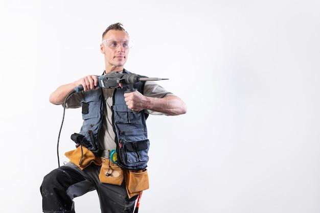 Il muratore con un trapano in mano, in fase di scarico, mira a destra. per qualsiasi scopo.