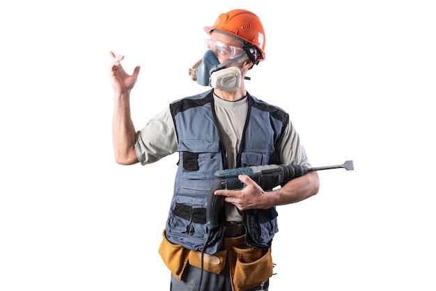 Il muratore con il trapano perforatore, in un casco, indica a sinistra. per qualsiasi scopo.