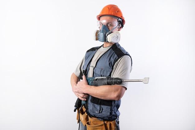 Il costruttore con un perforatore in un casco e un respiratore sta con il dispositivo nelle sue mani