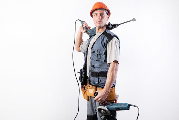 Un muratore con un trapano a percussione sulla spalla e una smerigliatrice angolare nell'altra mano, con indosso un casco, sorride. per qualsiasi scopo.