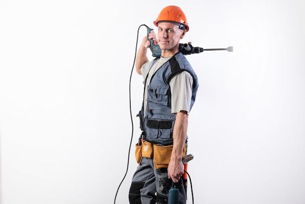 Un muratore con un trapano a percussione sulla spalla, in un casco, sorride. per qualsiasi scopo.