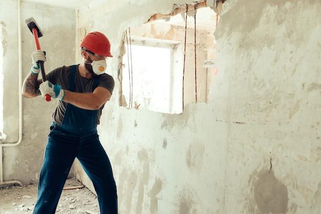 Il costruttore con un martello in mano rompe il muro di cemento