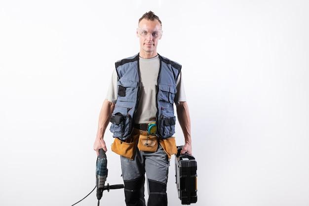 Builder con strumenti in una custodia e un trapano in mano. per qualsiasi scopo.
