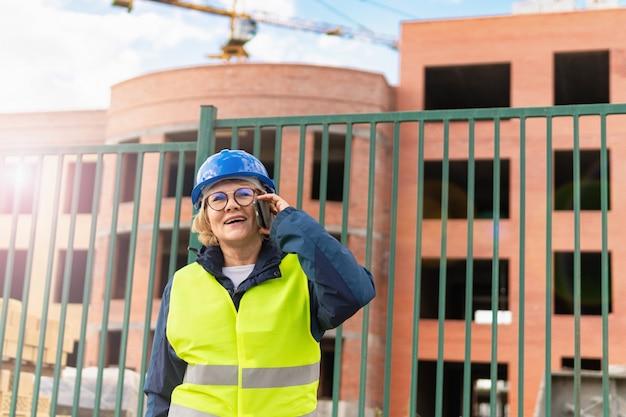 Donna del costruttore sul cantiere in giubbotto verde e casco blu con tablet. donna di mezza età con gli occhiali parlando al telefono.