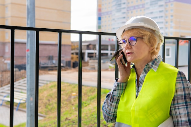 Donna del costruttore in cantiere con un giubbotto verde e un casco bianco, parla al telefono. una donna di mezza età con gli occhiali e una camicia a quadri contro il recinto.
