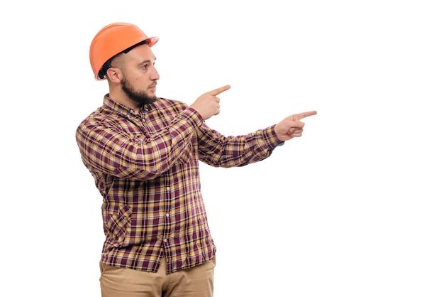 Operaio del costruttore nelle mani del casco arancio della costruzione protettiva che indica a destra, isolato su fondo bianco. copia spazio per il testo. ora di lavorare.