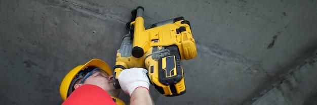 Il costruttore lavora a soffitto con perforatore per calcestruzzo. le pistole di montaggio per calcestruzzo sono strumenti a profilo stretto e vengono utilizzate da costruttori professionisti. guida di tasselli e chiodi su superfici dure
