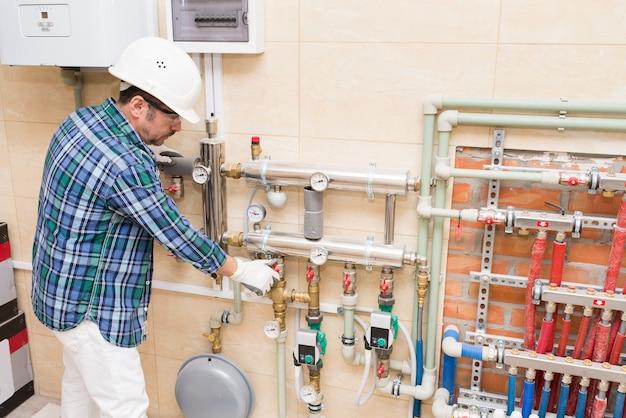Un muratore riparatore un idraulico sta installando il riscaldamento autonomo in casa uno scaldabagno una caldaia