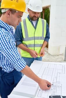 Costruttori che controllano le planimetrie sul cantiere