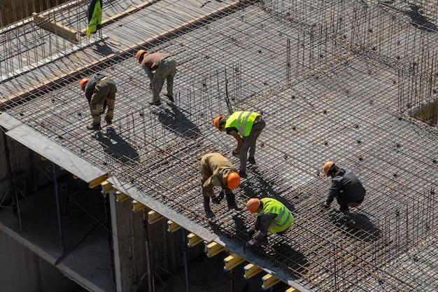 I costruttori in elmetti e giubbotti protettivi lavorano nel cantiere di un edificio a più piani