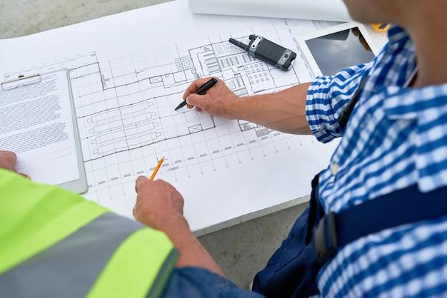 Costruttori che esaminano le planimetrie