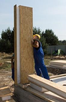 Costruttori che posizionano un pannello a parete verticale con uno spesso isolamento in un cantiere per una nuova casa di costruzione