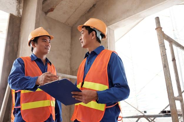 Costruttori in uniforme che discutono il piano di lavoro per il giorno in cui si incontrano in cantiere