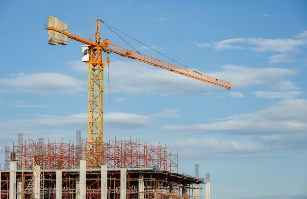 Costruendo in costruzione e gru a torre contro il cielo blu. concetto di industria.