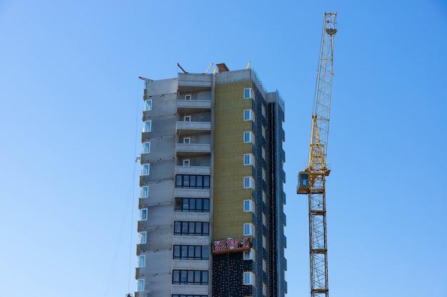 Edificio in costruzione, flusso di lavoro, progetti di costruzione, isolamento e finitura di facciate.